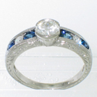 Platinum diamond ring with 0.62 carat round brilliant diamond in bezel setting on hand-engraved tapered-channel shank with 0.30 carat total weight of round blue sapphire melee and 0.20 carat total weight of round diamond melee