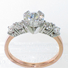 2-tone engagement ring with 5 round brilliant diamonds set in 4-prong platinum heads on 14 karat rose gold square-stock shank. Center stone= 0.66 carat round brilliant diamond