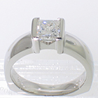 "Platinum solitaire with 1.01 carat princess-cut diamond in ""bracket-style"" semi-bezel on polished heavy shank"