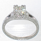 Platinum hand-engraved split-shank ring with 1 carat round brilliant diamond in 12-prong fishtail-style fancy head and 0.10 carat total weight of round melee diamonds in shank