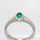 Platinum Solitaire ring with oval-shaped caboschon-cut emerald in full bezel setting