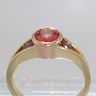14 Karat 2-tone Yellow and Rose Gold 3-stone ring with round Padparadscha Sapphire in full bezel setting and orange diamonds channel-set into split-shank