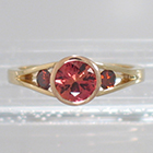 14 Karat 2-tone Yellow and Rose Gold 3-stone ring with round Padparadscha Sapphire in full bezel setting and orange diamonds channel-set into split-shank (alternate view)