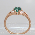 "14 Karat Rose Gold 3-stone ring with round Emerald in 6-prong ""gallery"" style setting with round white diamonds channel-set into split-shank"