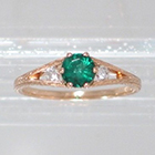 "14 Karat Rose Gold 3-stone ring with round Emerald in 6-prong ""gallery"" style setting with round white diamonds channel-set into split-shank (alternate view)"