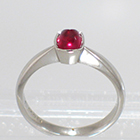 Palladium solitaire ring with cushion-shaped bullet-caboschon-cut Ruby in full bezel setting