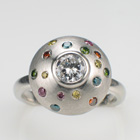 Platinum pillow-style ring with flush set colored diamonds in brushed metal finish.