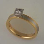platinum + 18 karat yellow gold band with princess-cut diamond in tapered full bezel.
