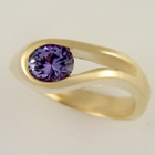 yellow gold oblong channel-set oval purple sapphire ring.