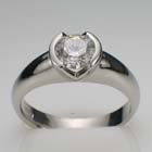 platinum ring with 1.09 carat round diamond in split-bezel setting on thick rounded shank.