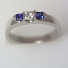 platinum ring with princess-cut diamond in saddle and two princess-cut sapphires set with triangular bars