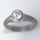 1ct. set into a bezel on a textured tapered band