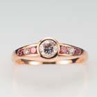 14 karat rose gold ring with a bezel-set round diamond and a tapered channel of alternating pink and colorless diamonds.