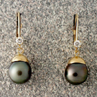 dangle earrings with black pearls and diamonds in 14 karat yellow gold.