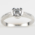 Platinum hand-engraved ring with 0.52 carat round diamond in semi-bezel.