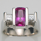 Platinum ring with channel-set cushion-cut pink sapphire and two princess-cut diamonds.